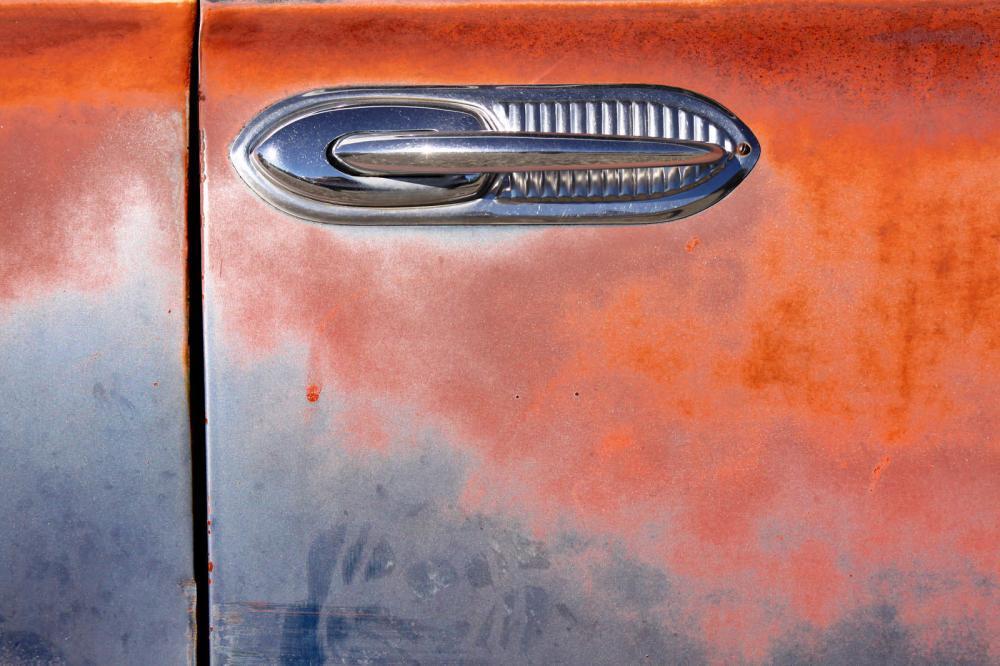 Closeup of door handle belonging to the rusted car.