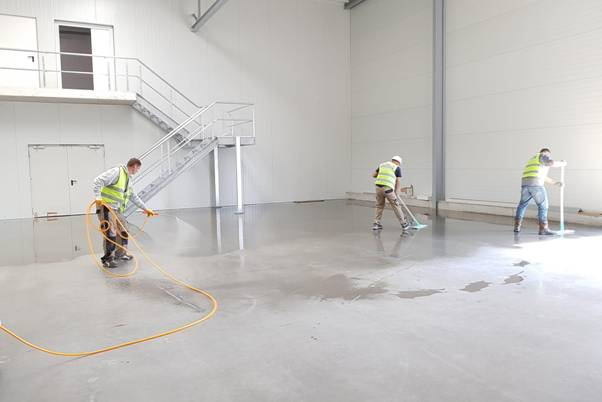 Construction workers cleaning and maintaining flooring