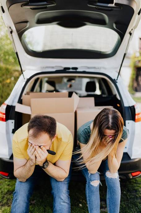 A stressed-out couple sits in the trunk of a car, looking flustered and upset.