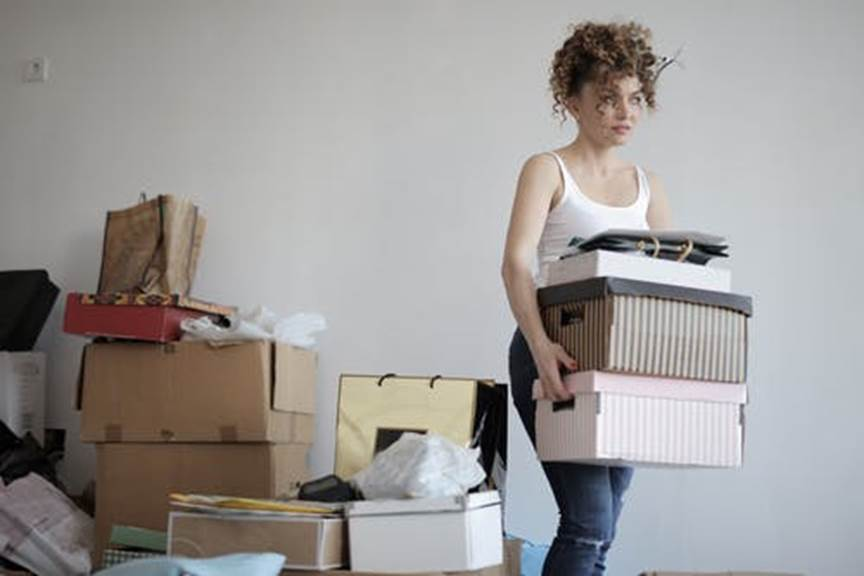 A woman carries boxes from a messy stack as she packs.