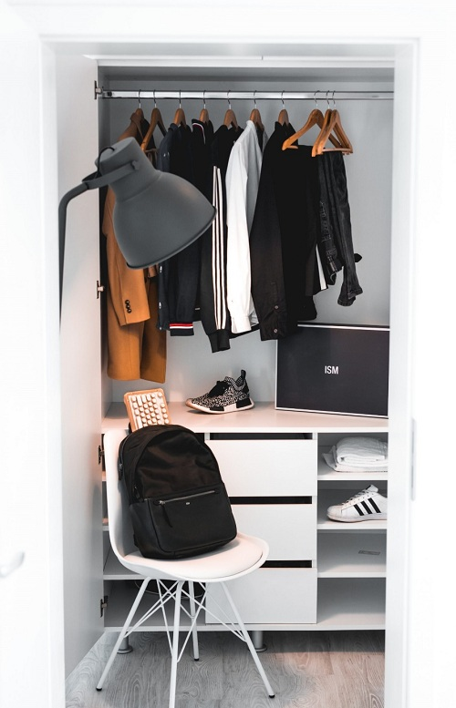 A custom closet displays hanging clothes and shoe sections